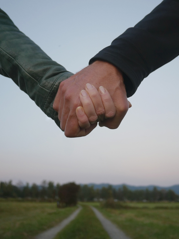 couple holding hands in front of a path